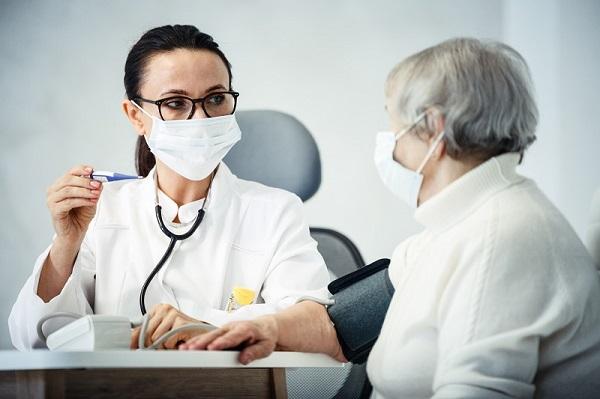 Ärztin spricht mit älterer Patientin, wobei beide eine Maske tragen