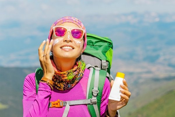 Wanderin trägt Sonnenschutz im Gesicht auf
