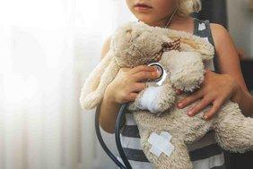 kleines Mädchen hört Plüschhasen mit Stethoskop ab