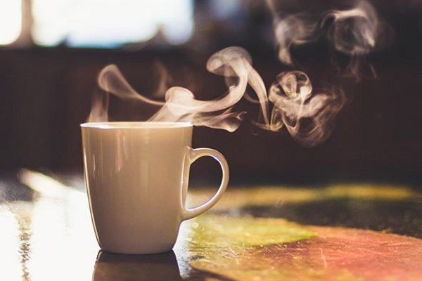 eine weiße Tasse mit heißem Tee steht auf einem Tisch