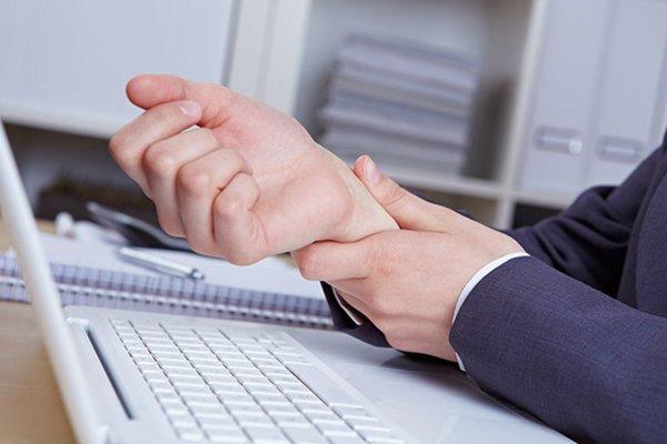 eine Frau hält sich mit der linken Hand das rechte Handgelenk wegen Schmerzen; vor ihr steht ein Laptop