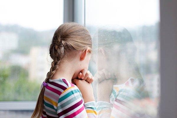 ein kleines Mädchen steht mit dem Rücken zum Betrachter und sieht traurig aus dem Fenster