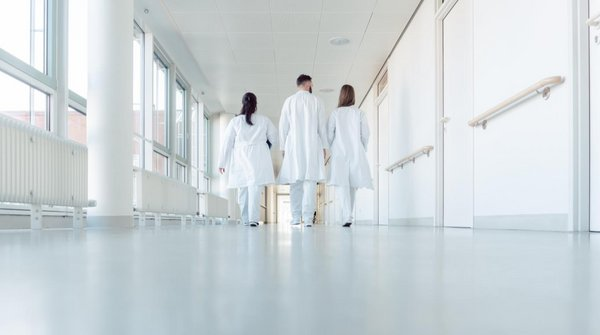 Krankenhausgan, an dessen Ende drei Ärzte gehen